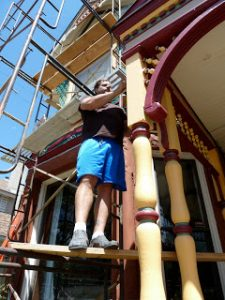 My husband painting our Queen Anne Victorian. Photo credit Charlie Trentleman