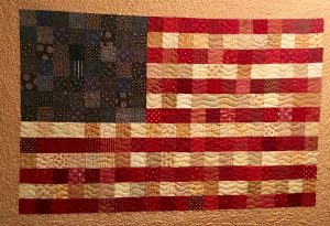 Quilt of a United States flag made by Becky Lockhart and hanging in their home. She made many quilts and gave them to loved ones.