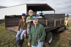 Three generations of men on the back of a truck on the family farm. Telling business stories with purpose passes values from generation to generation.