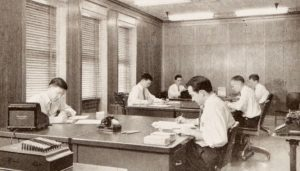 Men doing office work in the 1940s. Maybe their responsibilities included transcribing audio to text with a dictaphone. What do you think?