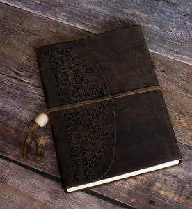 Many problems are solved when you read words out loud. Photo of a beautiful leather bound book on a wooden table.