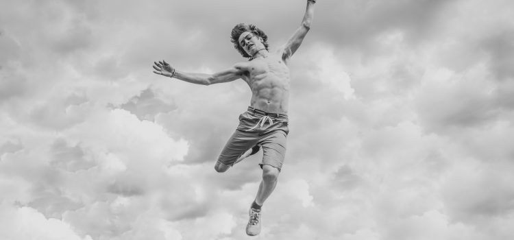 A young man joyfully leaping, a wonderful image of overcoming obstacles. Photo by Shane Rounce on Unsplash