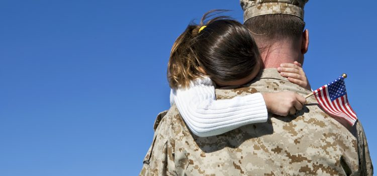Military man hugs his daughter. On Veterans Day we appreciate the sacrifice our servicemen and women make away from their families.
