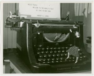 Transcribe audio to text using voice recognition tools, which are a wee bit faster than the old typewriter method. This is a vintage image of a woman standing on a giant typewriter.