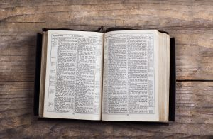 Curate a canon of business stories for your organization. Photo of an antique book, maybe a bible, on a weathered wood table.